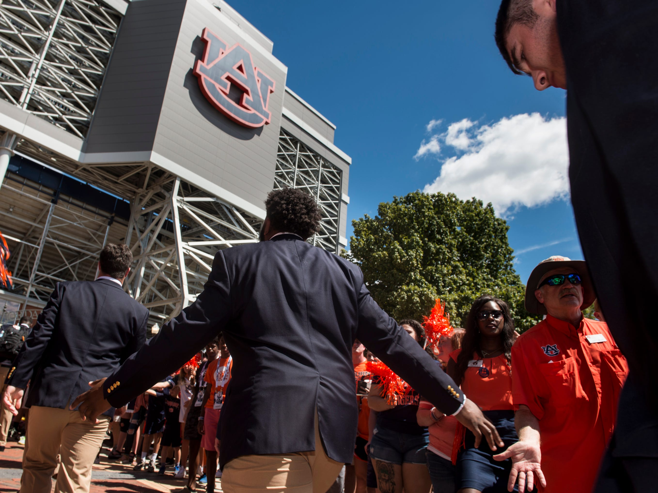 Players high five fans during the Tiger Walk outside Jordan-Hare Stadium in Auburn, Ala., on Saturday, Sept. 15, 2018.