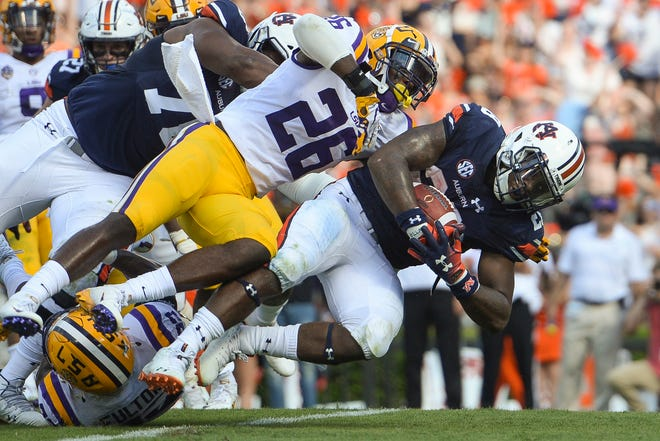 Auburn running back JaTarvious Whitlow (28) pushes past LSU Tigers safety John Battle (26) to score a touchdown on Sept. 15, 2018, in Auburn, Ala.