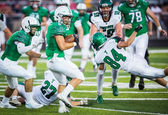 FILE -- New Castle's Tytus Ragle runs the ball against Yorktown's defense during their game at New Castle High School on Sept. 14, 2018.