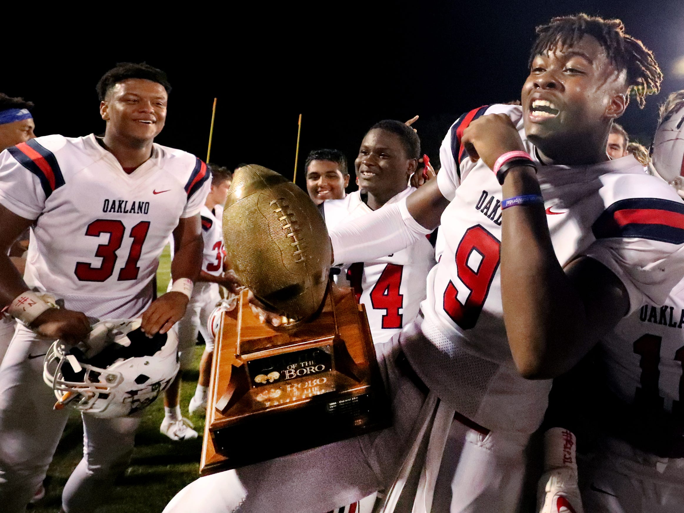 Oakland's Tekoy Randolph (9) celebrates the teams win with the Battle of the Boro trophy after beating Riverdale 49-6 during the Battle of the Boro on Friday, Sept. 14, 2018.
