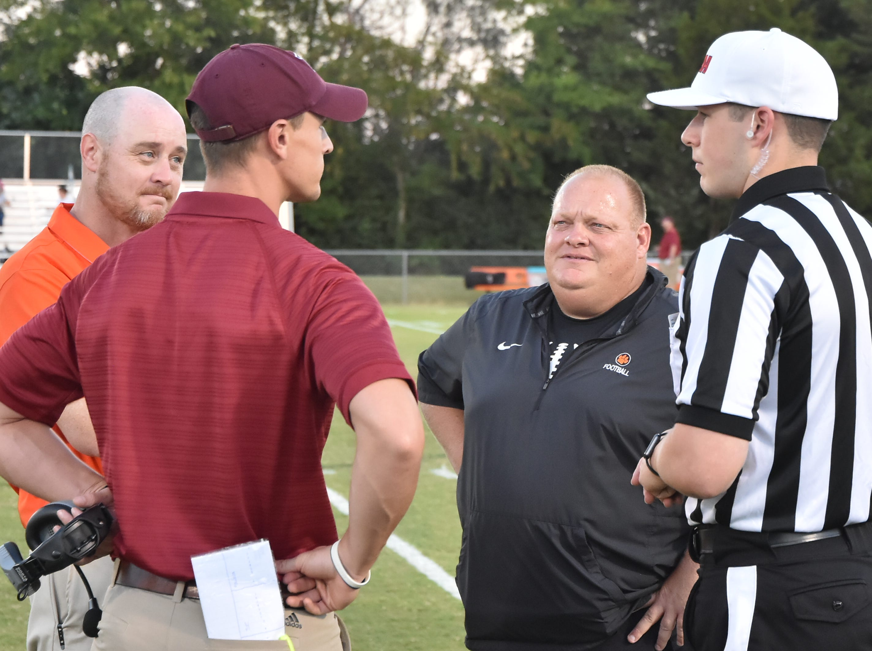 MTCS Head Coach Fred Shambaugh and Ezell-Harding Head Coach Dustin McGee talk with the referee and MTCS Athletic Director Jason Piercy Friday night before their football game.