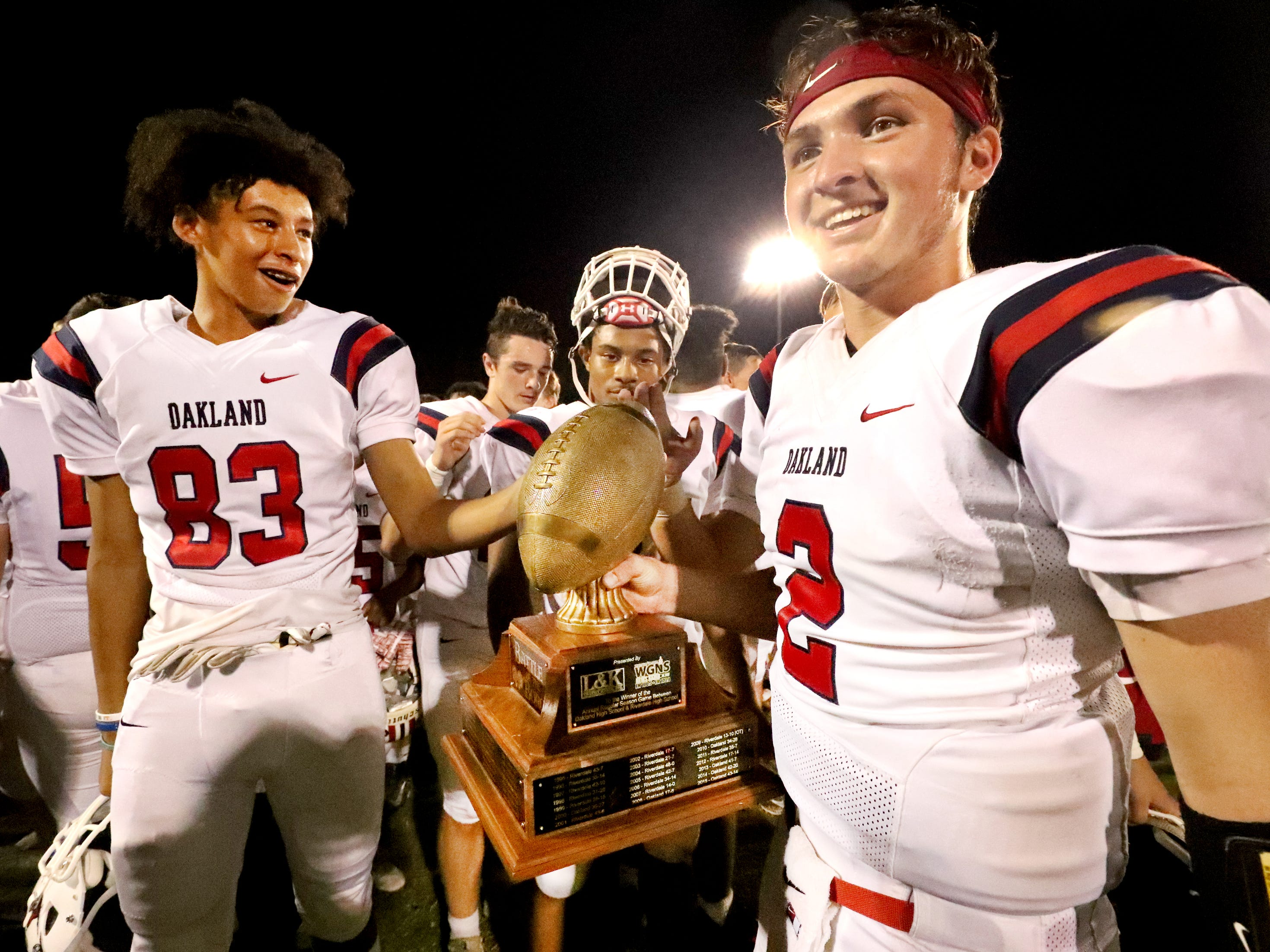 Oakland's Brevin Linnell (2) shows off the Battle of the Boro trophy before receiving the MVP of the game trophy after beating Riverdale 49-6 during the Battle of the Boro on Friday, Sept. 14, 2018.