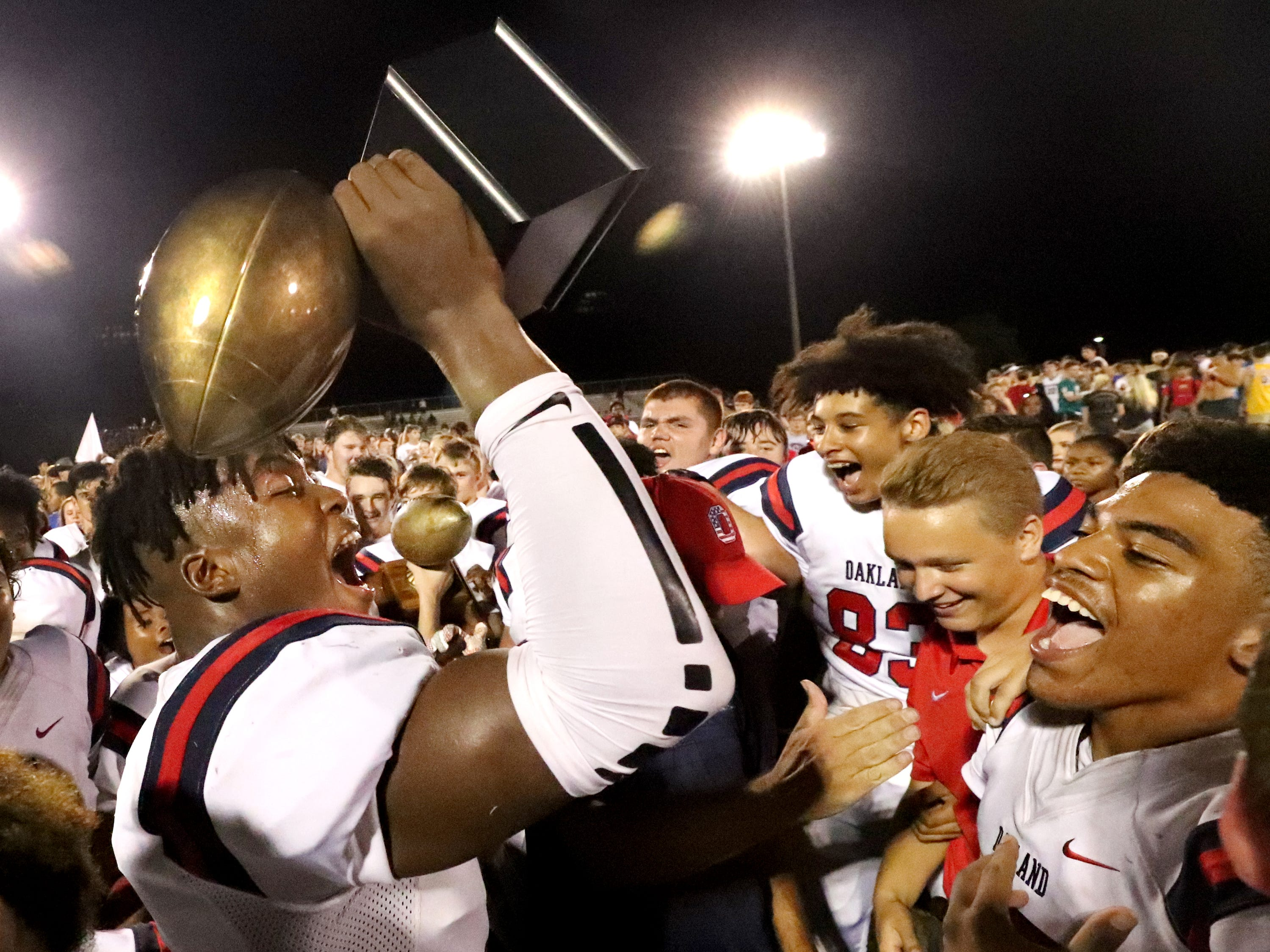 Oakland's Tekoy Randolph (9) celebrates the teams win with the Friday Night Rivals Championship trophy after beating Riverdale 49-6 during the Battle of the Boro on Friday, Sept. 14, 2018.