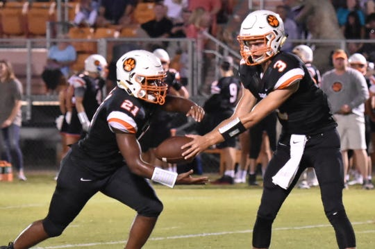 MTCS quarterback Jackson Green hands off to running back Kemari McGowan during a recent game.