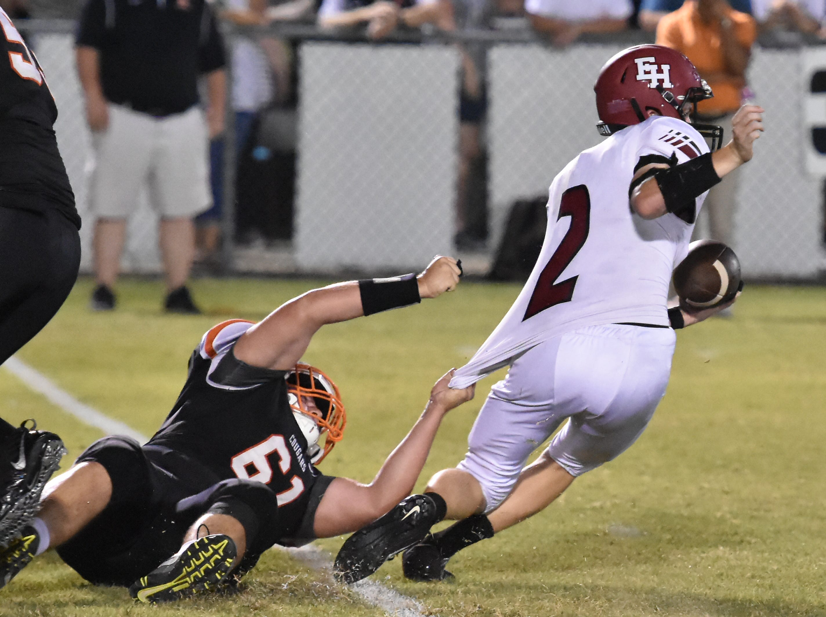 Daniel Templeton of MTCS holds on to the jersey of Ezell- Harding QB Derik Griffin Friday night.