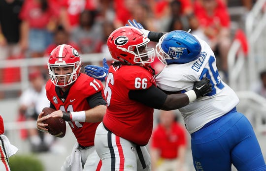 Georgia quarterback Jake Fromm (11) tries to escape from Middle Tennessee defensive lineman Rosheem Collins (96) offensive lineman Solomon Kindley (66) blocks in the first half of an NCAA college football game, Saturday, Sept. 15, 2018, in Athens, Ga. (AP Photo/John Bazemore)