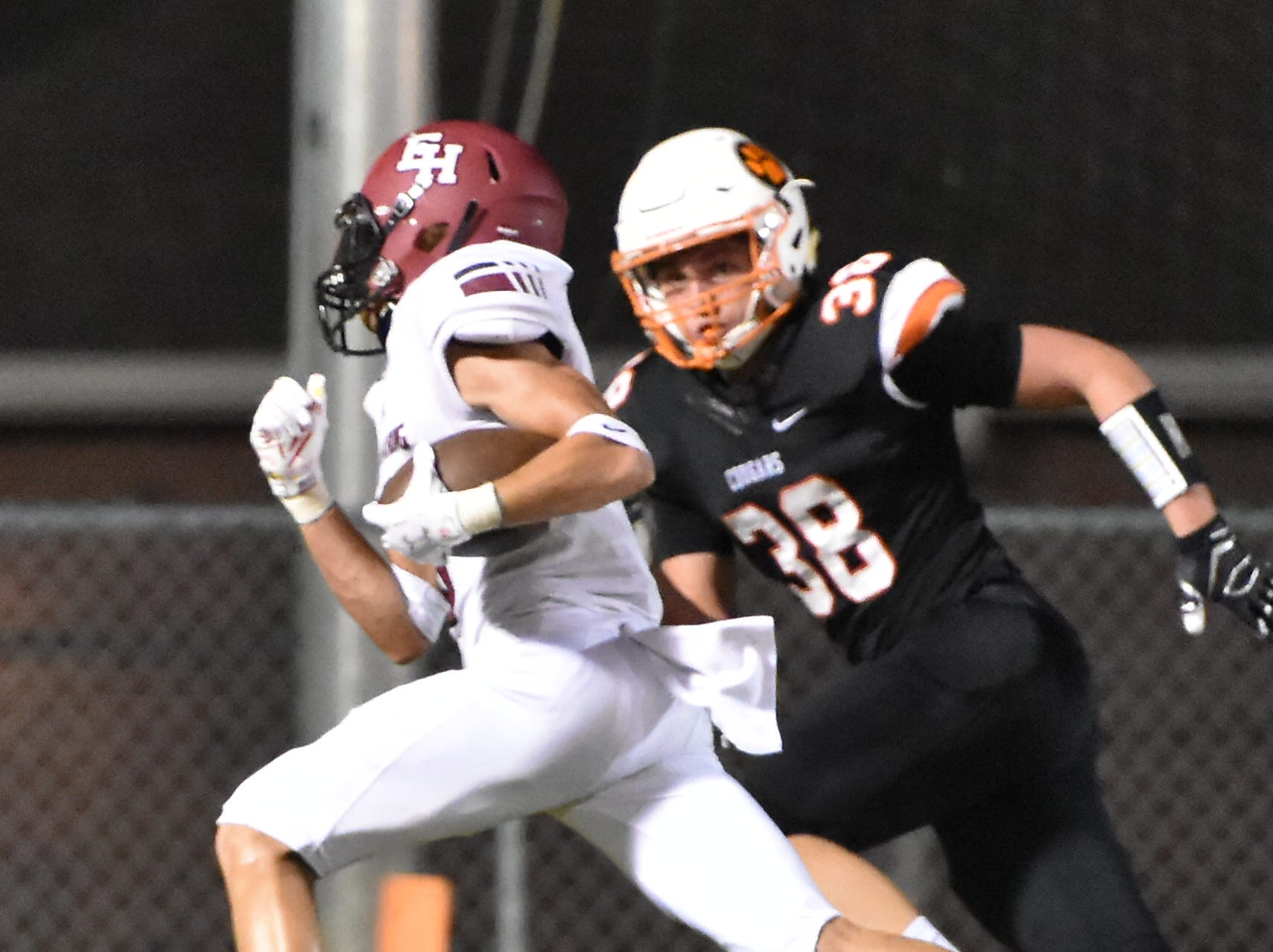 Ezell-Harding QB Derek Griffin runs toward the end zone as MTCS's Hudson Tate moves in Friday night.