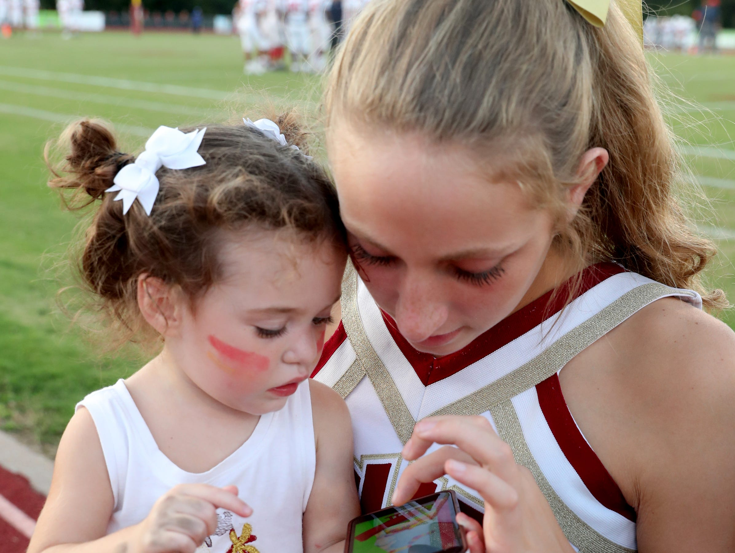 Charlie Brooke, 2, plays on a phone with Riverdale cheerleader Shelby Turek before the game between Oakland and Riverdale, during the Battle of the Boro, on Friday, Sept. 14, 2018, at Riverdale.