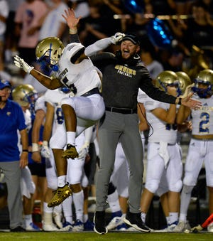 Brentwood wide receiver Chayce Bishop celebrates with a coach after pulling in a pass for a touchdown against Ravenwood during the second half of a high school football game Friday, September 14, 2018, in Brentwood, Tenn. Brentwood won 31-28.