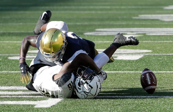 Notre Dame safety Jalen Elliott, top, breaks up a fourth-down pass to Vanderbilt wide receiver Kalija Lipscomb late in the game on Sept. 15, 2018.