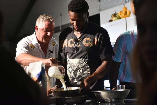 Kevin Byard is helped by Tim Love craft biscuits during the Nashville Food & Wine Festival Friday Throwdown between Predators and Titans.
