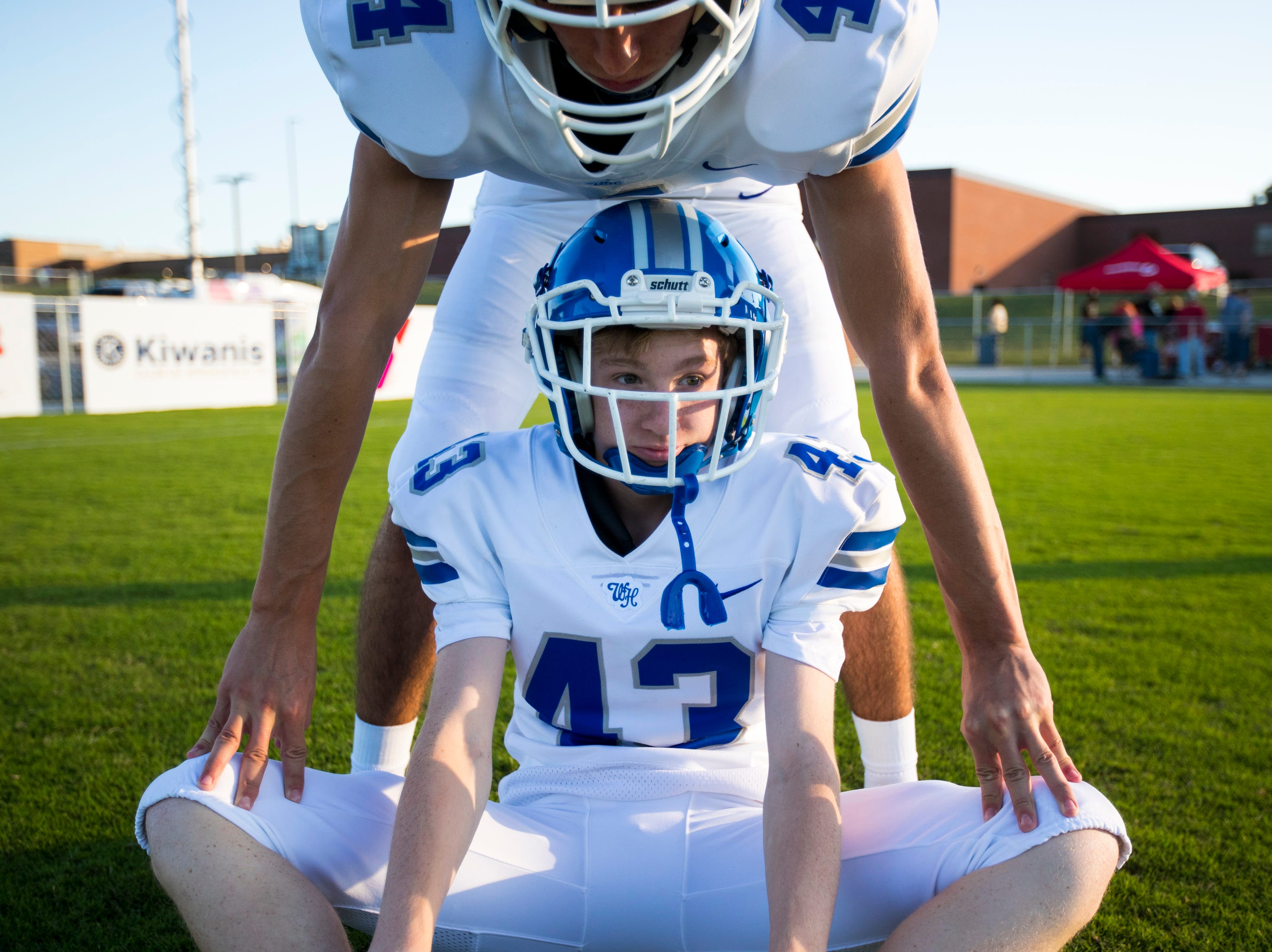 A teammate helps White House's Matthew Miller (43) stretch before Springfield's game against White House at Springfield High School in Springfield on Friday, Sept. 14, 2018.