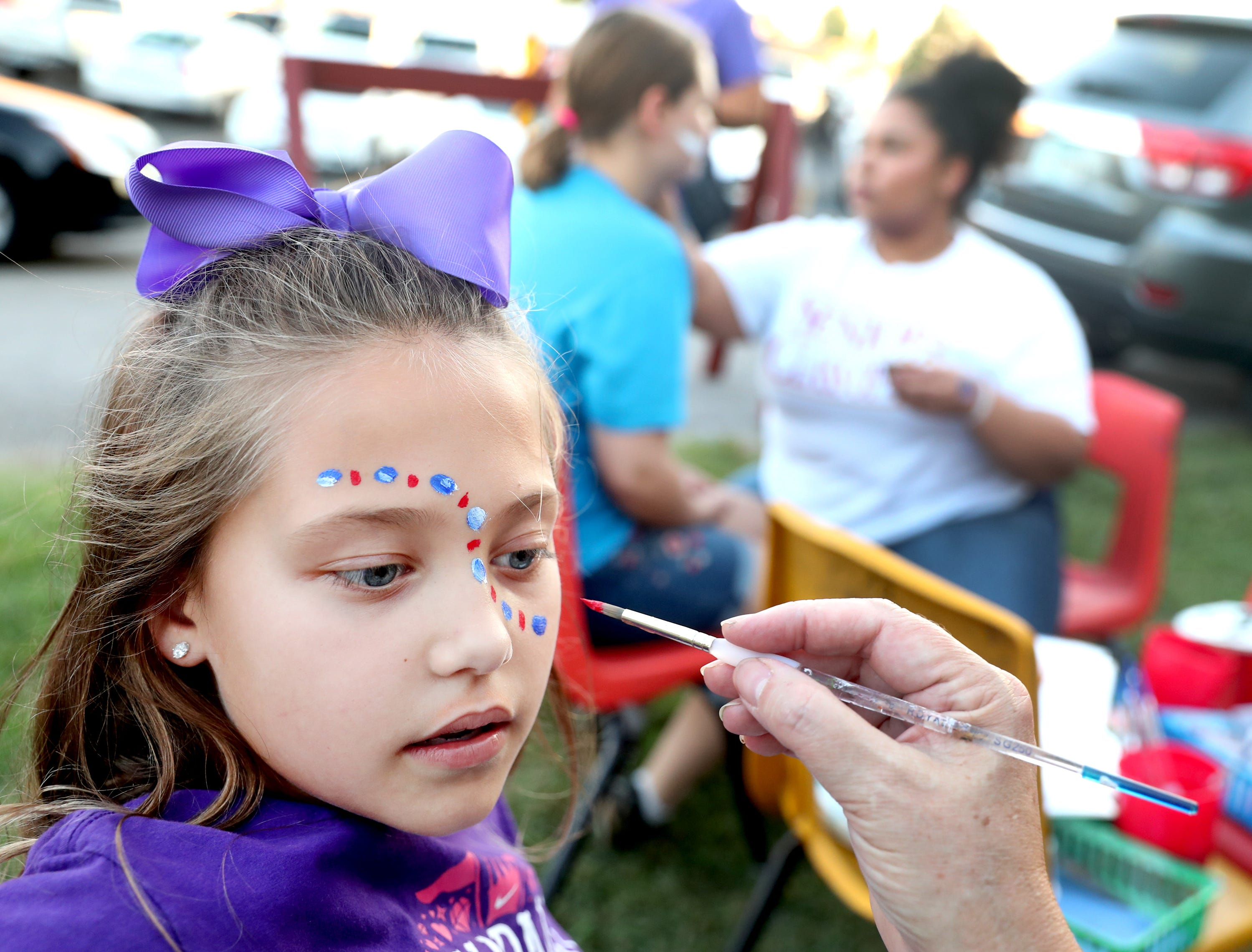 Rilyn Rice, 8, Oakland fan gets her face painted by Riverdale art teacher Carrie Perkins before the game between Oakland and Riverdale, during the Battle of the Boro, on Friday, Sept. 14, 2018, at Riverdale.