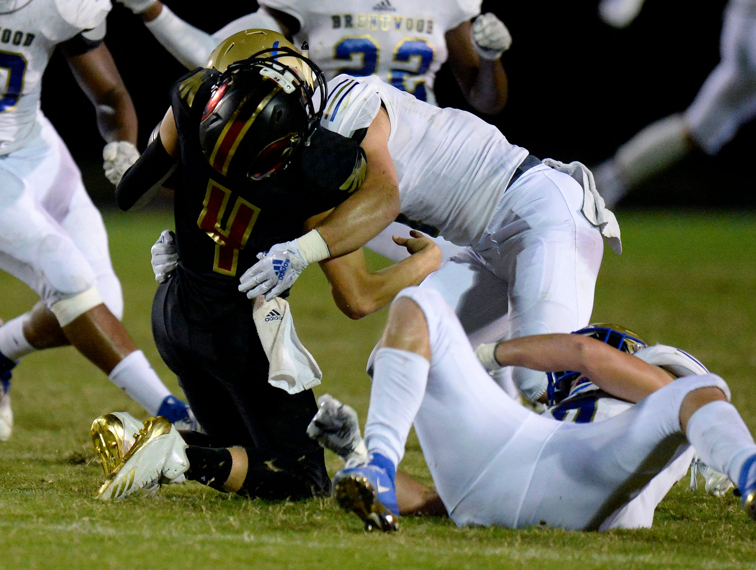 Ravenwood quarterback Brian Garcia (4) is tackled by Brentwood defenders during the first half of an high school football game Friday, September 14, 2018, in Brentwood, Tenn.