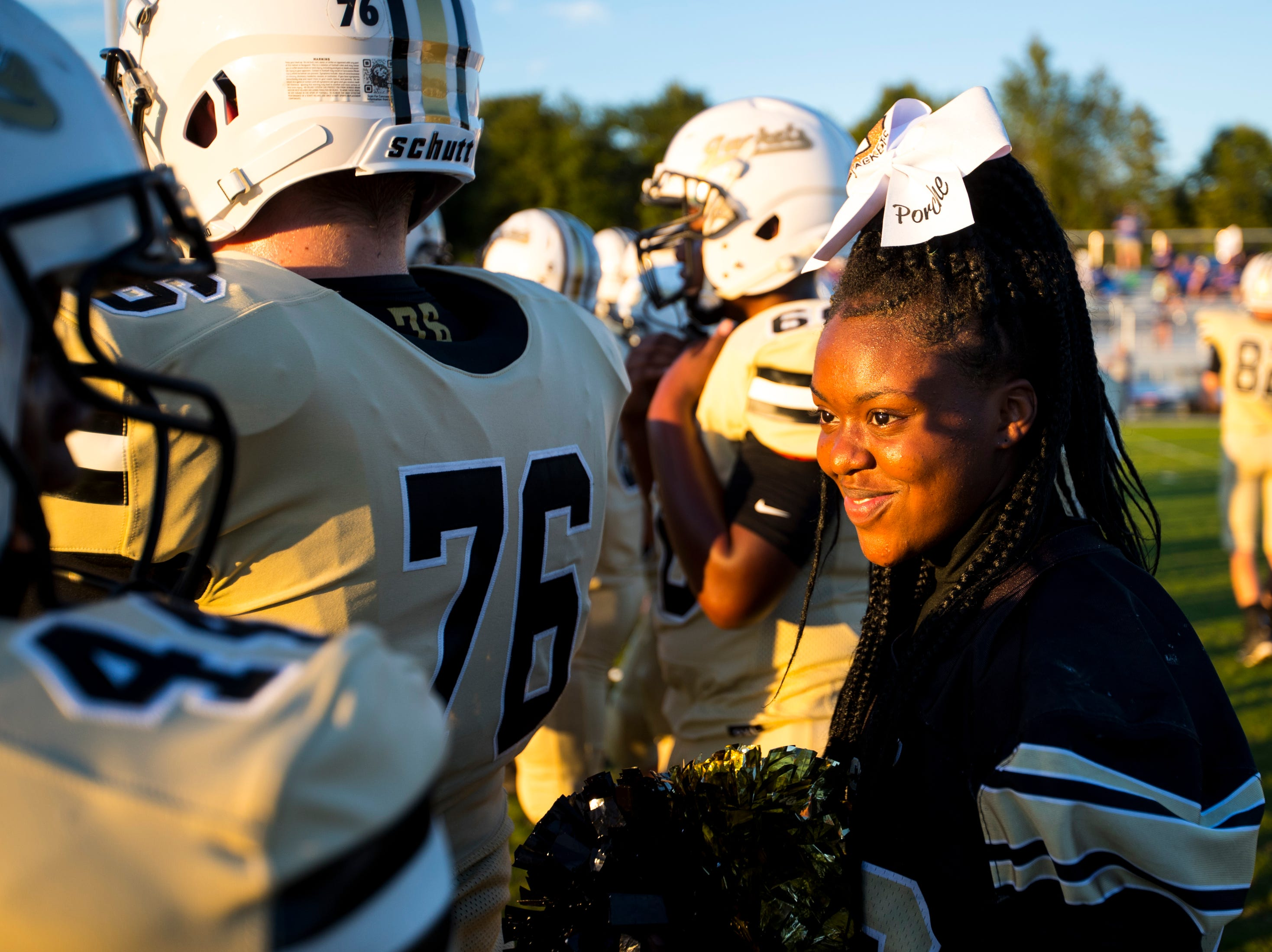 Springfield cheerleader Porche Chatman smiles while talking to Springfield's Martavious Johnson (44) before Springfield's game against White House at Springfield High School in Springfield on Friday, Sept. 14, 2018.