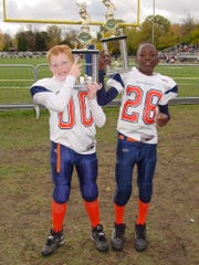 Corey Davis, right, and friend Ryan Graham hold up trophies during their youth football days.