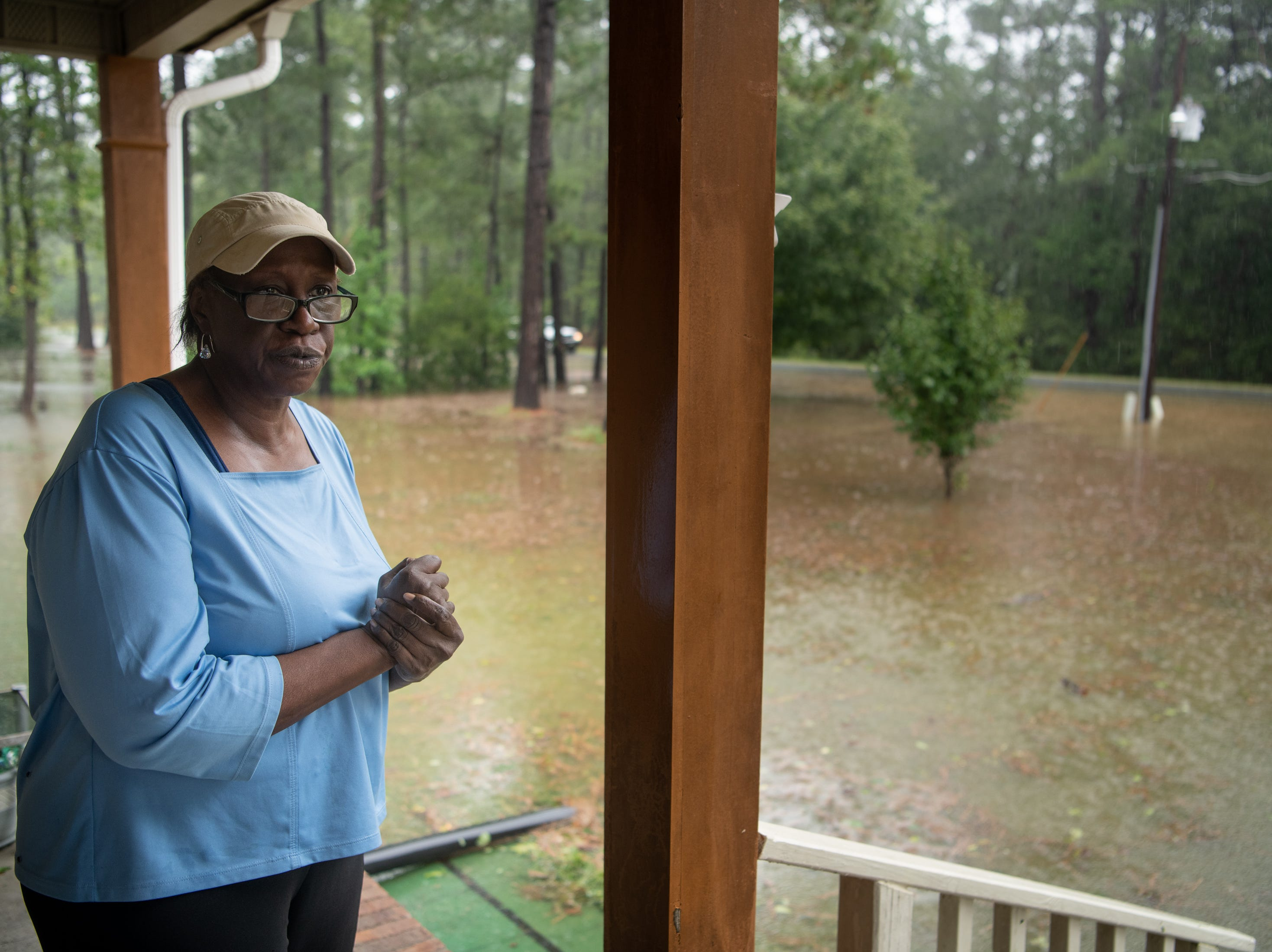 Mittie Wooten watches her flooded front yard as rain from Tropical Storm Florence continues to fall on Lumberton, N.C., Saturday, Sept. 15, 2018.