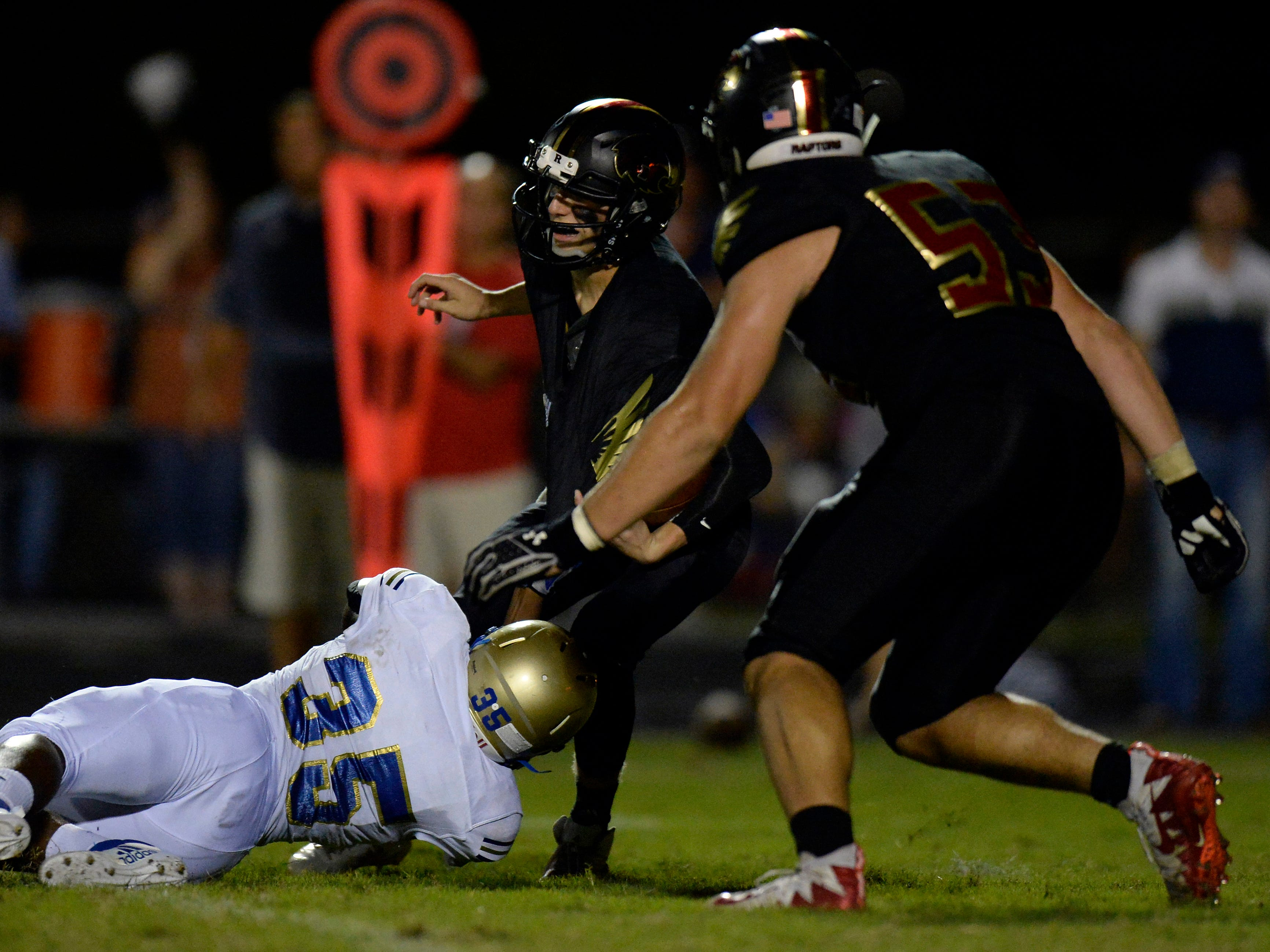 Brentwood linebacker Kaleb Williford (35) sacks Ravenwood quarterback Brian Garcia, center, during the second half of a high school football game Friday, September 14, 2018, in Brentwood, Tenn. Brentwood won 31-28.