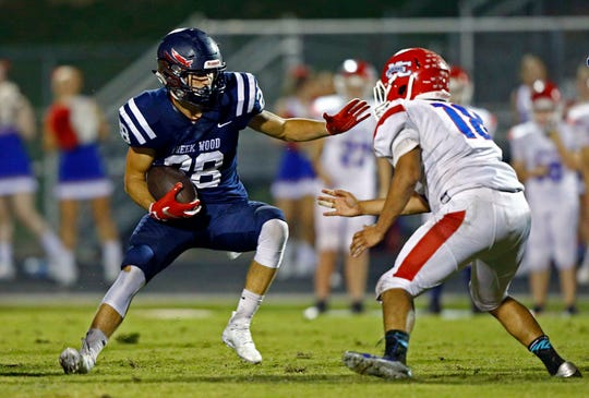 Creek Wood's Garrett Stansberry (28) runs for yardage as he's defended by Montgomery Central's Marquel Stacker (18) during their game Friday, Sept. 14, 2018, in Charlotte, Tenn.