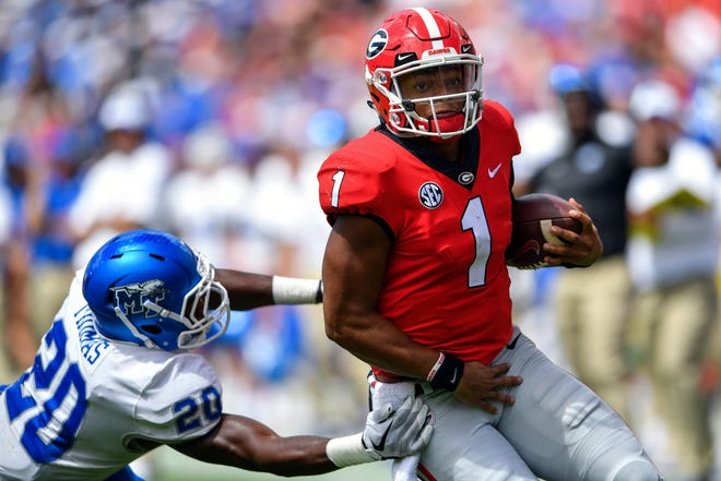 Sep 15, 2018; Athens, GA, USA; Georgia Bulldogs quarterback Justin Fields (1) breaks a tackle by Middle Tennessee Blue Raiders linebacker DQ Thomas (20) to score a touchdown during the first half at Sanford Stadium. Mandatory Credit: Dale Zanine-USA TODAY Sports