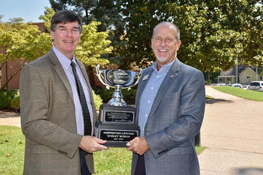 Lipscomb Academy headmaster Greg Glenn and Goodpasture president Ricky Perry hold the Martin-McCadams Cup. The trophy was award to Lipscomb Academy on Friday night after beating Goodpasture 28-0.