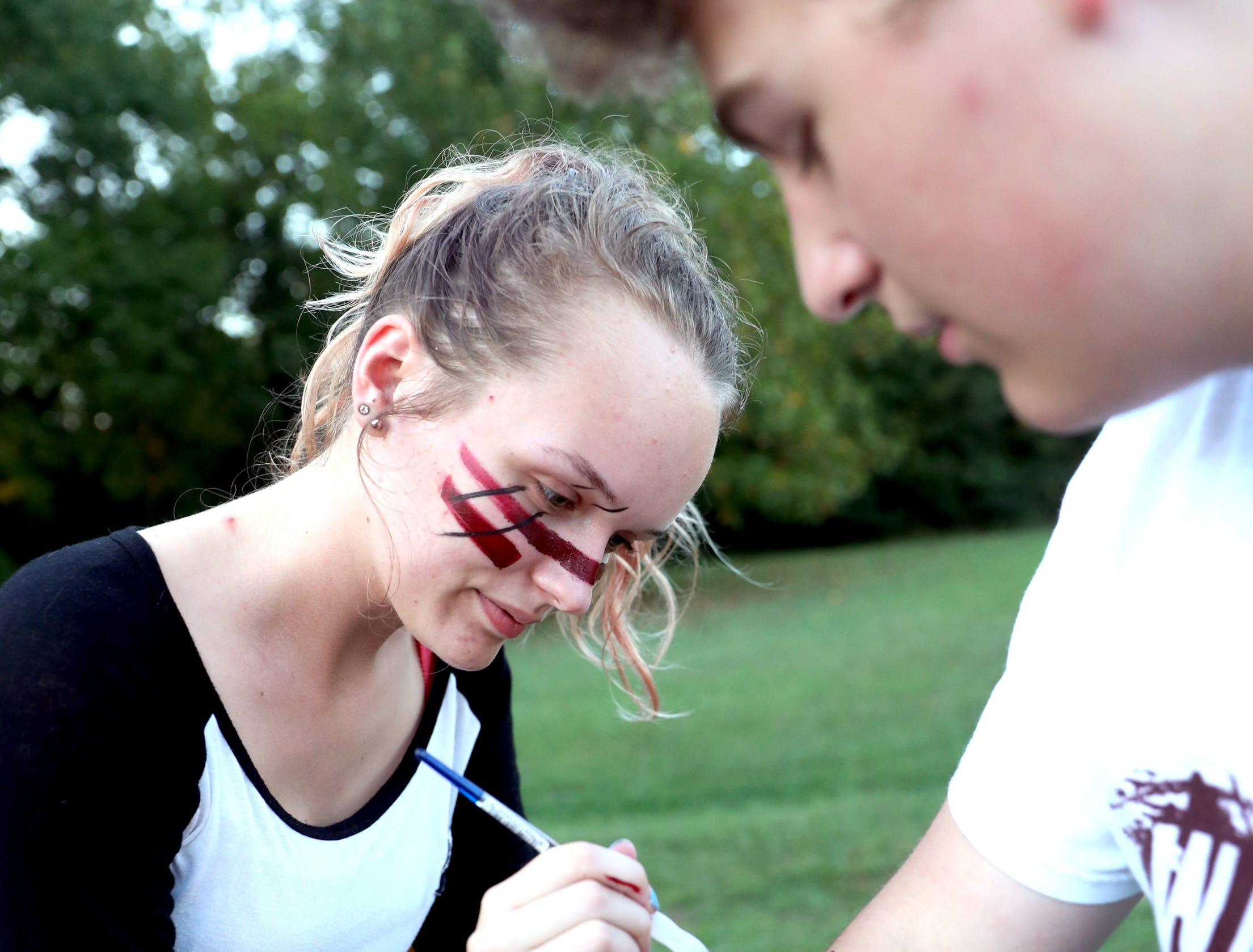 Riverdale junior Leala Sykes paints and arrow on the arm of Riverdale junior Lucas Orr before the game between Oakland and Riverdale, during the Battle of the Boro, on Friday, Sept. 14, 2018, at Riverdale.