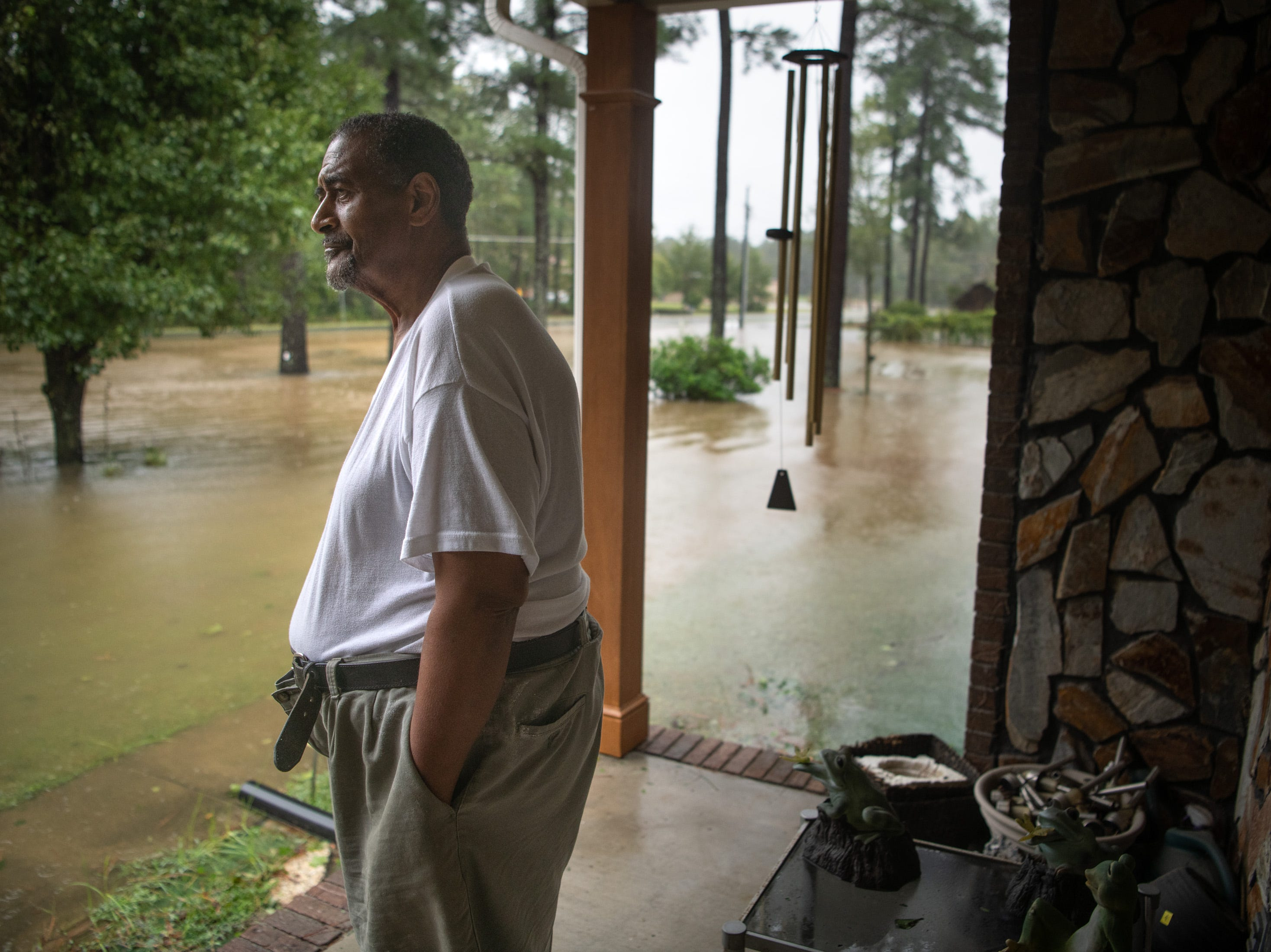 William Wooten watches his flooded front yard as rain from Tropical Storm Florence continues to fall on Lumberton, N.C., Saturday, Sept. 15, 2018.