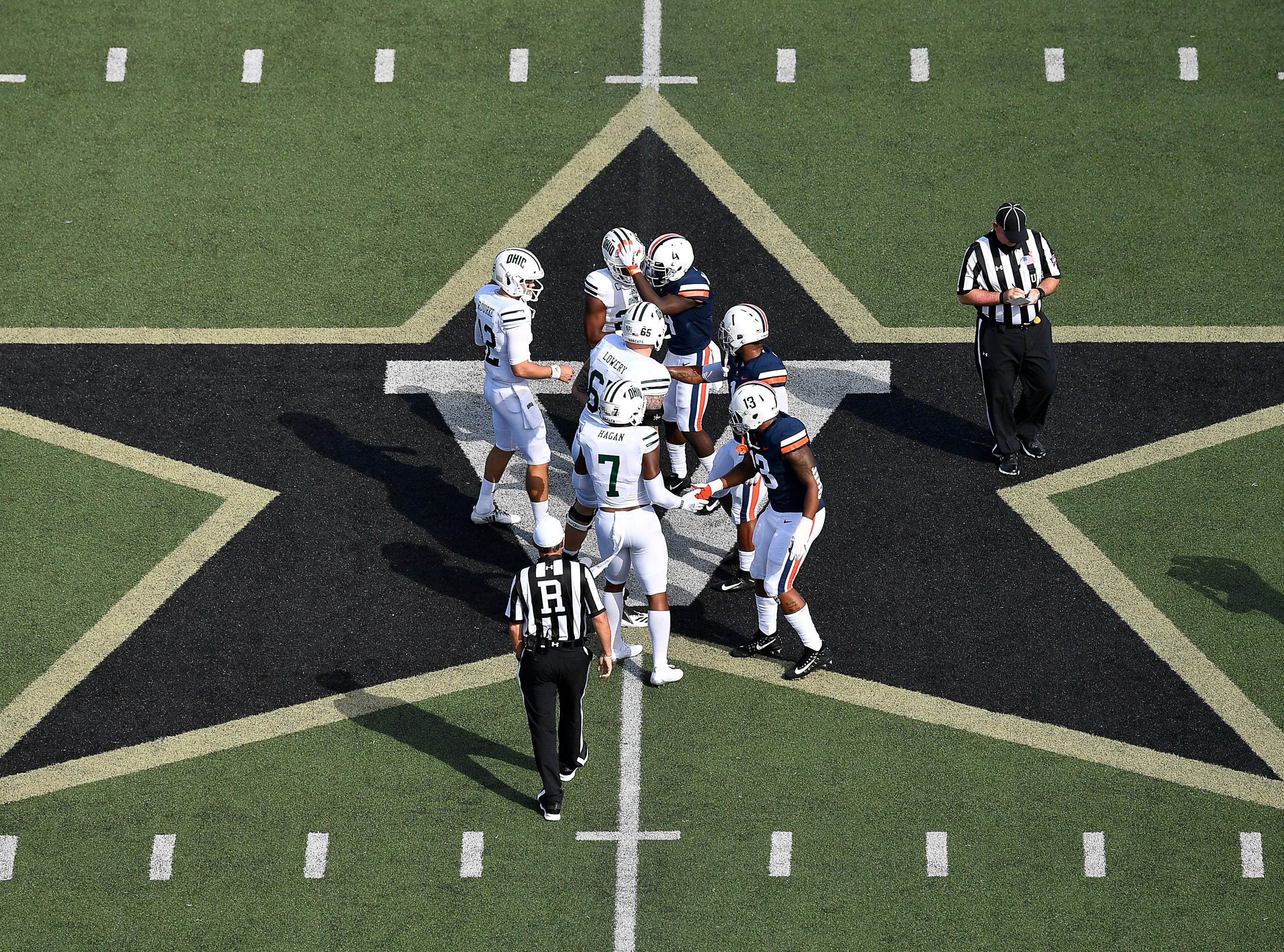 Virginia and Ohio players shake hands before there game at mid-field of Vanderbilt Stadium Saturday, Sept. 15, 2018, in Nashville, Tenn. Their football game was moved from Virginia to Tennessee to avoid the effects of Hurricane Florence.