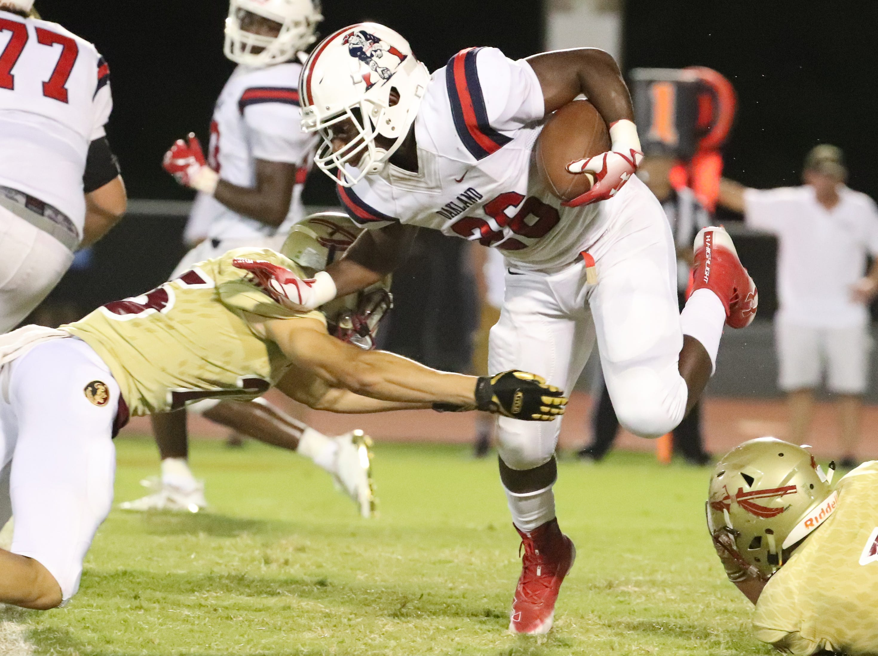 Oakland's Xavier Myers (26) runs the ball as Riverdale's CJ Johnson (25) moves in for a tackle at Riverdale during the Battle of the Boro on Friday, Sept. 14, 2018.