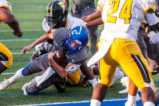 Barron Collier senior Jason Grimes (12) gets tackled after running the ball during the game against St. Petersburg-Lakewood at Barron Collier High School in Naples on Friday, Sept. 14, 2018.