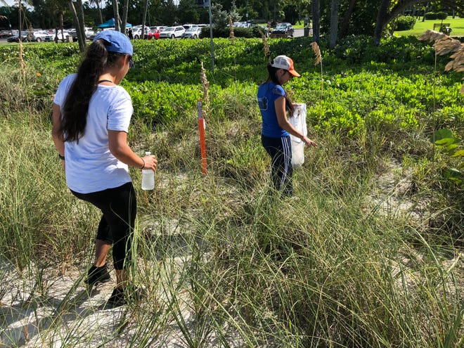 Jackie Loredo, left, cleans up trash with her sister, Juliana Loredo, right, on Sept. 15, 2018 at Lowdermilk Park. The sisters wanted to get involved to take care of what they loved, they said.