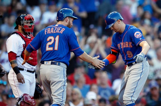 New York Mets' Brandon Nimmo (9) celebrates his three-run home run that also drove in Todd Frazier (21) as Boston Red Sox's Sandy Leon, left, looks on during the fourth inning of a baseball game in Boston, Saturday, Sept. 15, 2018.