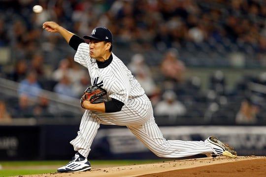 New York Yankees starting pitcher Masahiro Tanaka #19 pitches against the Toronto Blue Jays during the first inning at Yankee Stadium.