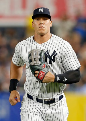 Sep 14, 2018; Bronx, NY, USA; New York Yankees right fielder Aaron Judge #99 runs in to the dugout against the Toronto Blue Jays during the eighth inning at Yankee Stadium.