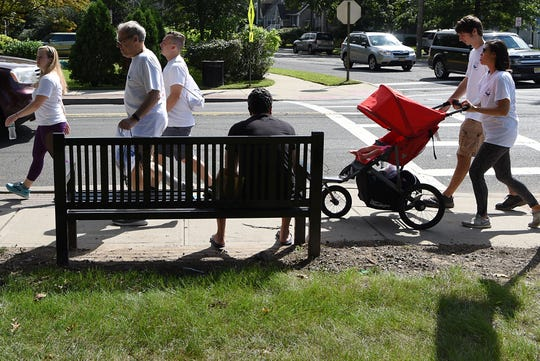 A man watches the from a bench, as th Darren Drake Memorial Walk passes him in New Milford on Saturday September 15, 2018.