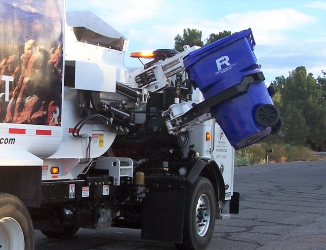 A truck picks up a blue recycling bin.