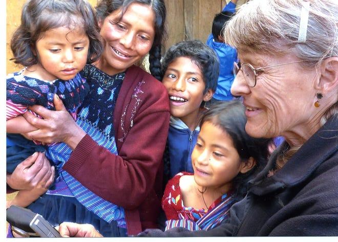 NMSU professor emeritus Christine Eber (right) shows a video she had taken to Lucia and her children.