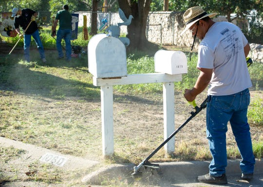 Volunteer Rigo Flores, with JL Gray Company, clears weeds at on Rainbow Road during a large clean up event coordinated by the Golden Shield Yard Assistance Program on Friday, September 14, 2018. Ten properties owned by disabled senior citizens were cleaned during the event.
