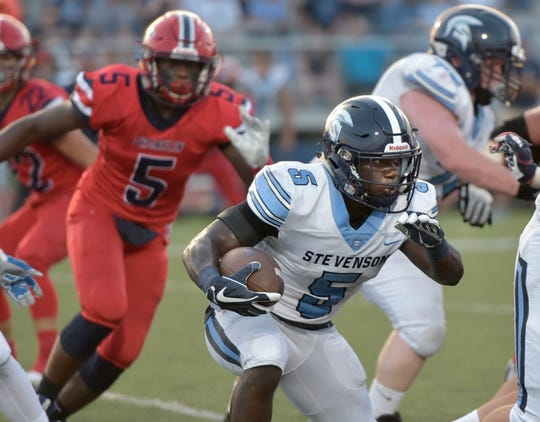 Stevenson's Dalen Cobb (with ball), chased by Franklin defensive end Arsell Weary, finished with 73 yards on 18 carries.