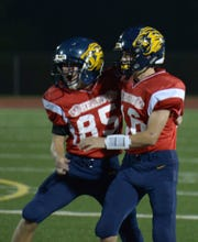 South Lyon's Connor Harris (85) is congratulated by teammate Connor McCollum (16) after he kicked the winning field goal with 5 seconds remaining.