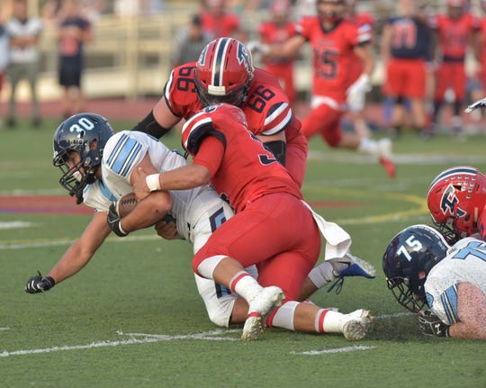 Stevenson's Evan Beck (30) tries to fight through Franklin tacklers Marino DiPonio and Jake Swirple.