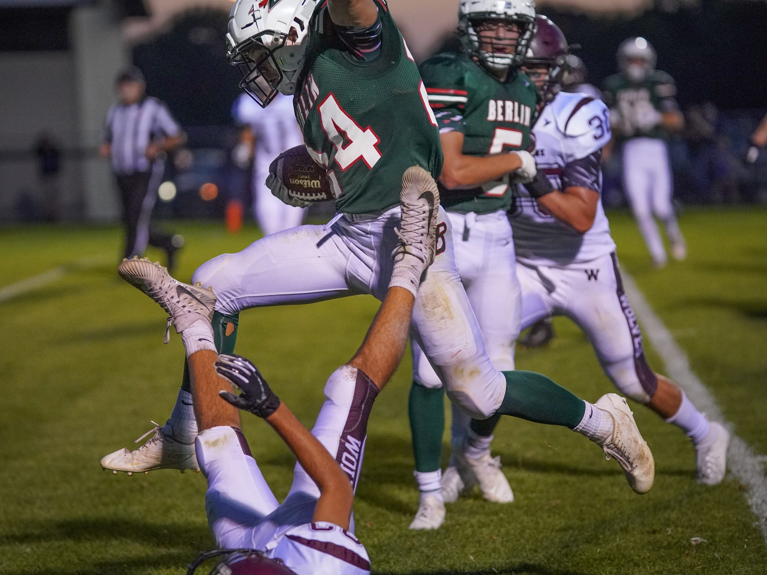 Aidan Schilling (24) of Berlin jumps over a Winneconne defender. The Berlin Indians hosted the Winneconne Wolves in an East Central Conference matchup Friday evening, September 14, 2018.