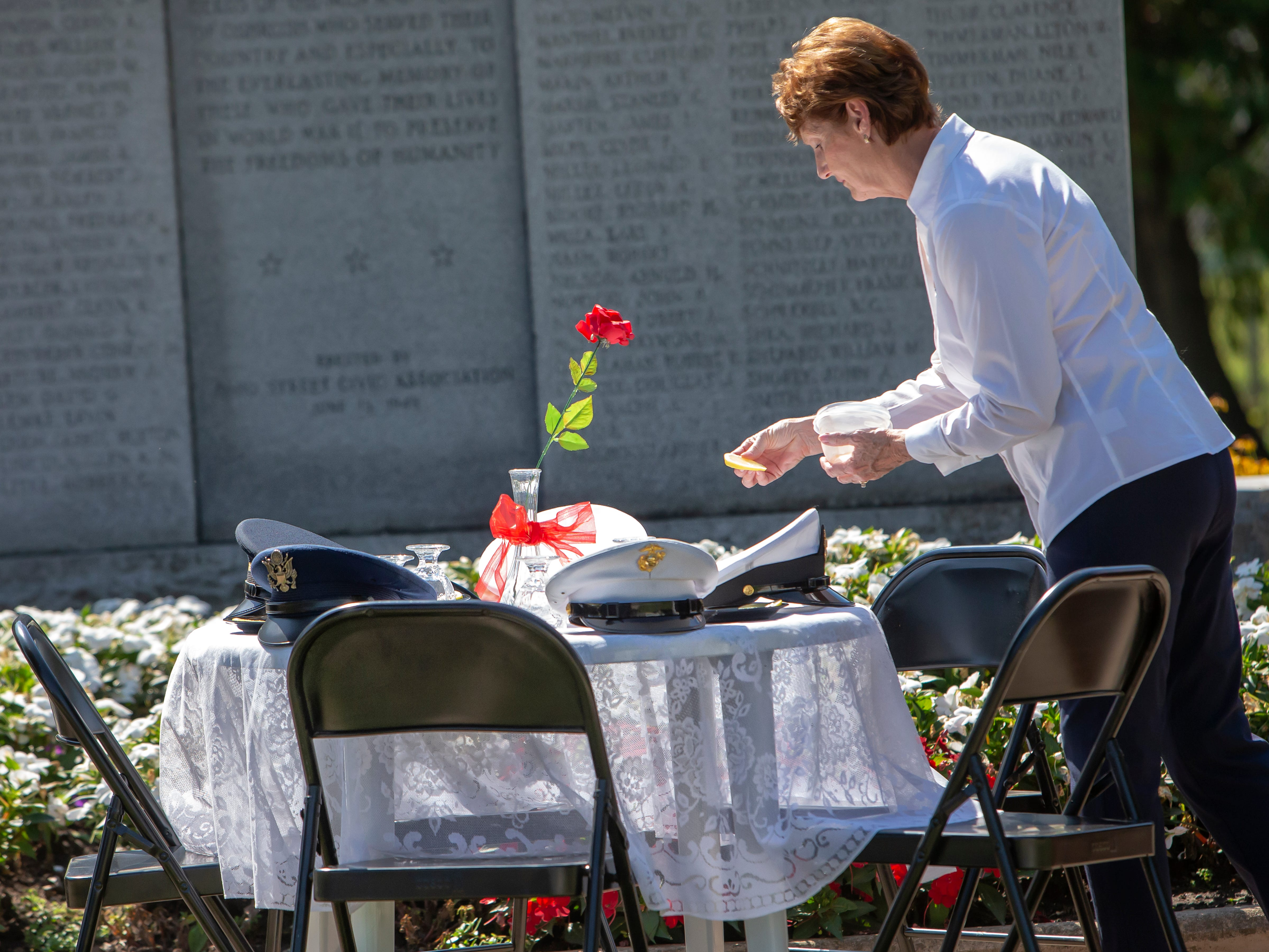 Lynn Beck places lemon slices and salt around the table ceremony honoring those still missing in action and prisoners of war during a POW MIA Remembrance Ceremony at South Park Veterans Memorial on Saturday, September 15, 2018.