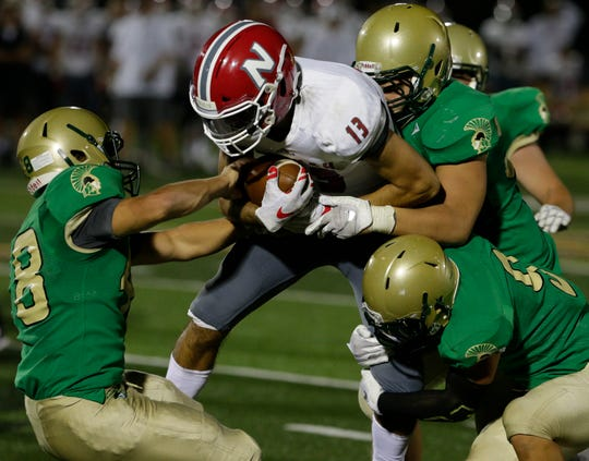 Neenah's Logan Morrow tries to break through the Oshkosh North defense on Sept. 14.