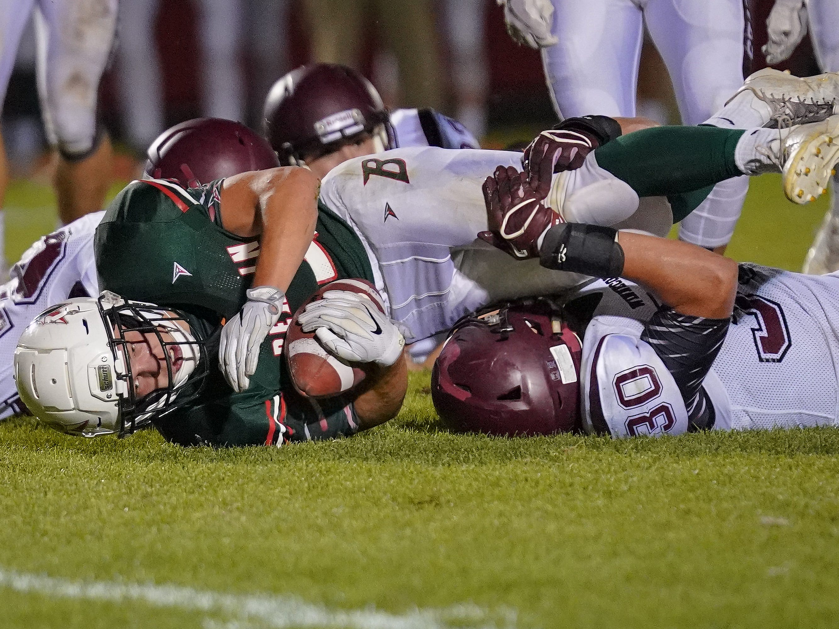 Aidan Schilling (24) of Berlin gets tackled by three Winneconne defenders. The Berlin Indians hosted the Winneconne Wolves in an East Central Conference matchup Friday evening, September 14, 2018.