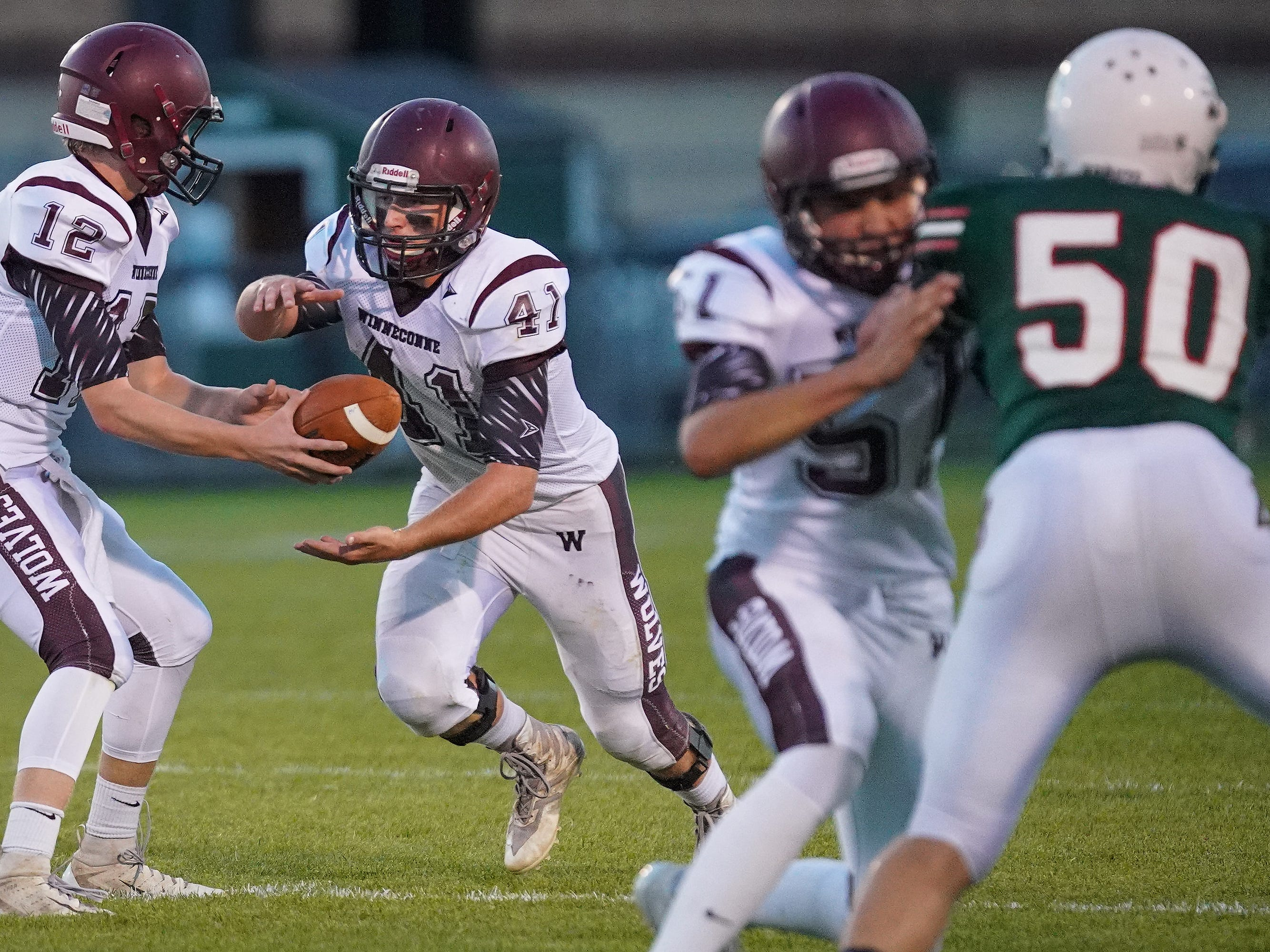 Wyatt Busching (41) of Winneconne takes the hand off from quarterback Harrison Roubidoux (12) in the first quarter. The Berlin Indians hosted the Winneconne Wolves in an East Central Conference matchup Friday evening, September 14, 2018.
