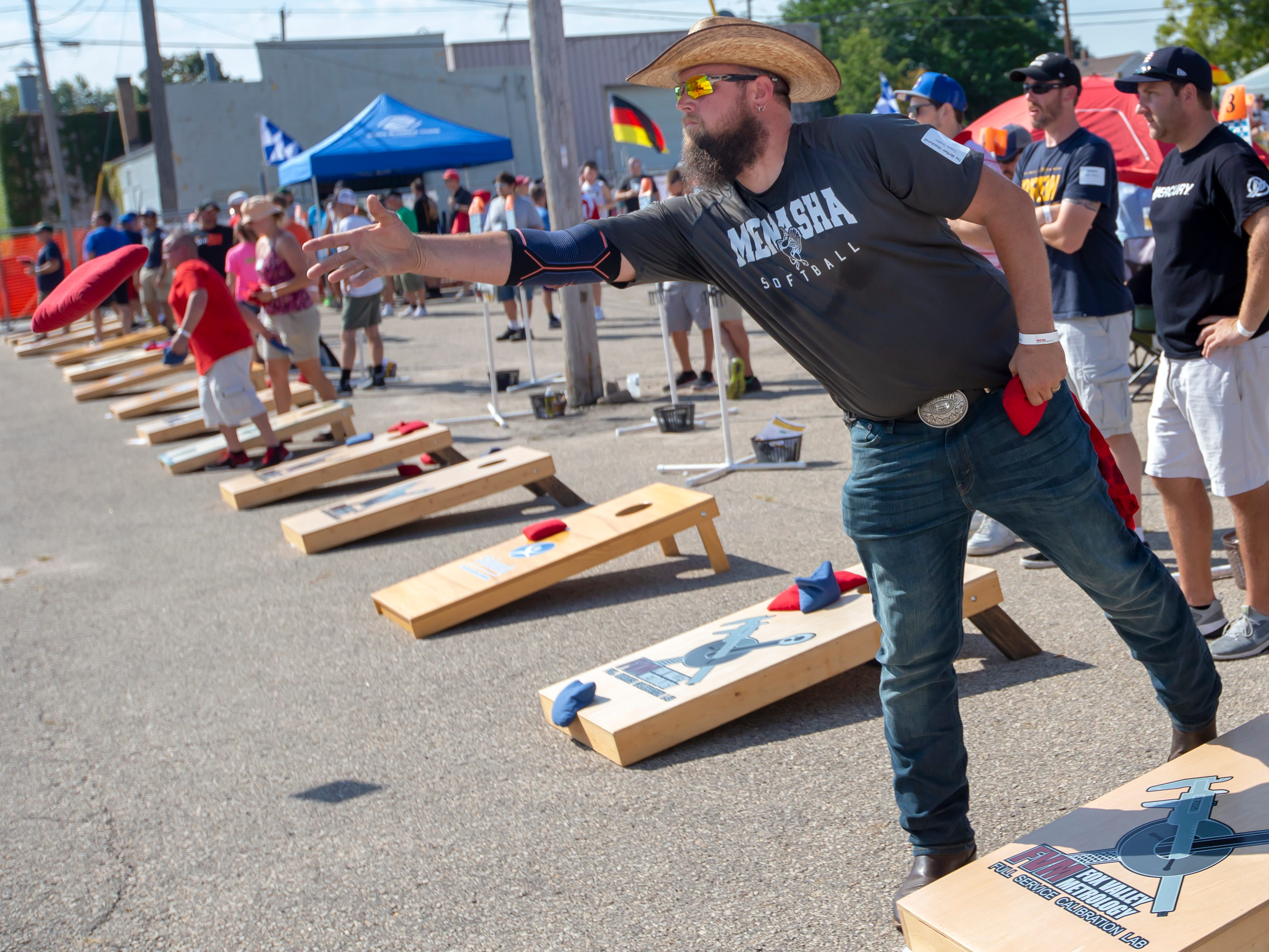 Travis Trader throws a red bean bag competing in the Wisconsin Cornhole Tourney at Dockside Tavern in Oshkosh on Saturday, Sept. 15, 2018.