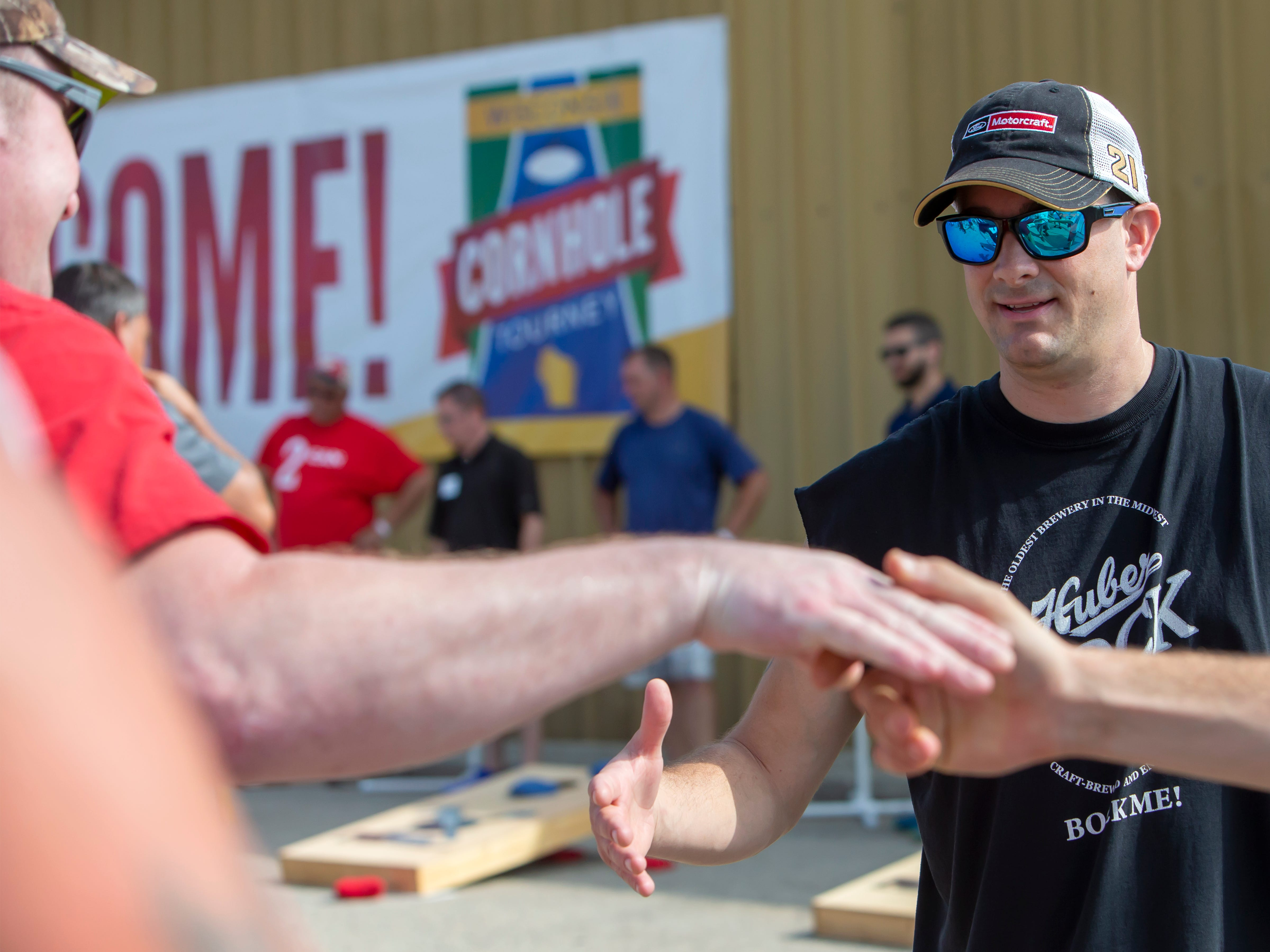 Mike Huber holds out his hand for an end-game handshake while competing in the Wisconsin Cornhole Tourney at Dockside Tavern in Oshkosh on Saturday, Sept. 15, 2018.