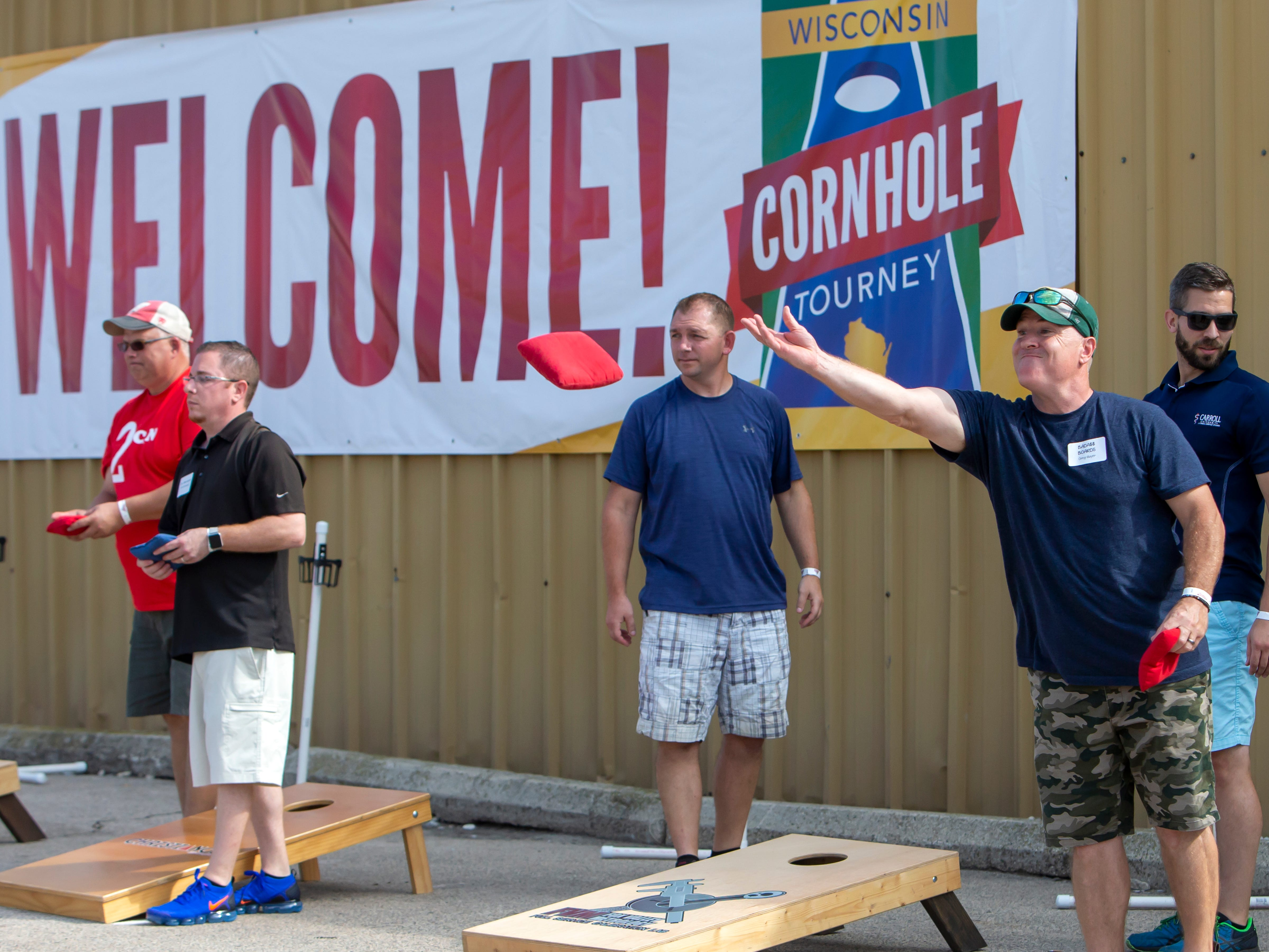 Greg Mayer tosses a red bean bag competing in the Wisconsin Cornhole Tourney at Dockside Tavern in Oshkosh on Saturday, Sept. 15, 2018.