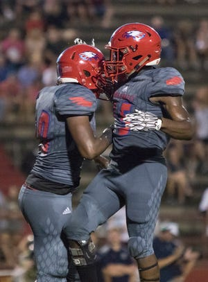 Taajhir Mccall (30) and Mitrez Rawls (15) celebrate after a big defensive play during the Gulf Breeze vs Pine Forest football game at Pine Forest High School in Pensacola on Friday, September 14, 2018.